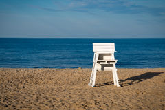 White lifeguard beach chair at Rehoboth Beach Delaware. Life Guard beach chair cast shadow on the sand with calm blue ocean water and sky in background stock image