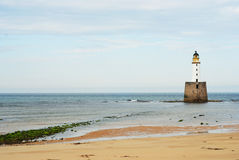 White lighhouse. White lighthouse, sand and green algae Stock Images
