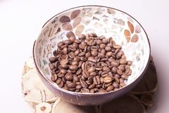 White light background. Coffee beans in a cup. Light brown plate Stock Image