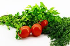 Three small red tomatoes placed with greens on a white background stock photos