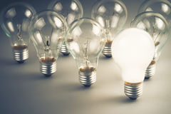 White light bulb. Glowing among the others Royalty Free Stock Images