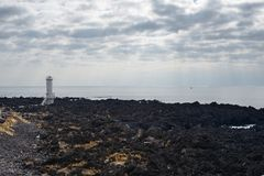 White Light House in basaltic seaside Royalty Free Stock Images