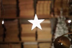 White light stars hanging, books shelves in the background royalty free stock images