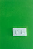 White light switch. Against a green wall Stock Photo