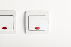 White light switch on/off on white wall with red led Stock Photo