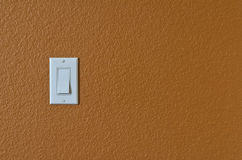 White light switch on orange wall Stock Photography