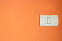 White light switch, turn on or turn off the lights on orange wal Royalty Free Stock Photo