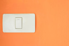 White light switch, turn on or turn off the lights on the orange wall Stock Images