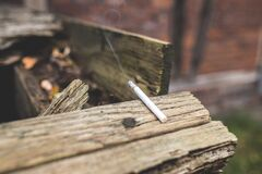 White Lighted Single Cigarette Stick on Beige Wood Stock Images