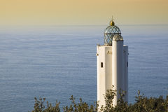 White lighthouse. View of a white lighthouse during daylight against the sea Stock Photography
