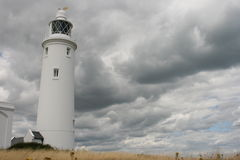 White Lighthouse. A tall white lighthouse on the backdrop of a cloudy sky Royalty Free Stock Images