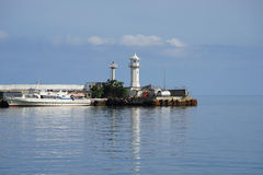 White lighthouse against the backdrop of quiet sea. White lighthouse on the background of calm Royalty Free Stock Photo