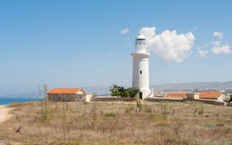White lighthouse against a blue sky. And mountains sunny summer day Royalty Free Stock Image