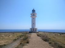 White lighthouse at the end of the road royalty free stock photo
