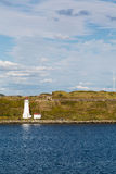 White Lighthouse on Green Coast by Blue Water. White lighthouse off the coast of Halifax, Nova Scotia Royalty Free Stock Photo