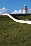 White Lighthouse on a green hill, Ireland Stock Photo