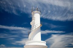 White lighthouse and intense blue sky with clouds royalty free stock image