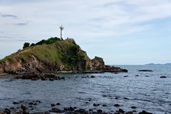 White lighthouse on a island in the sea Stock Photography