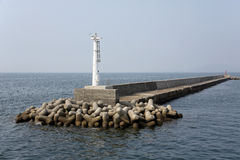 White lighthouse. With jetty in the sea Stock Photo