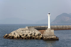 White lighthouse. With jetty in the sea Stock Image