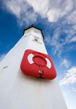 White lighthouse with lifering and blue skies Stock Photos