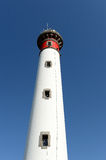 White lighthouse. Low angle view looking to top of white lighthouse with blue sky background Royalty Free Stock Images