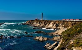 White Lighthouse Near Body of Water Under Blue Sky during Daytime Royalty Free Stock Photos