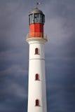 White lighthouse over dramatic sky. White lighthouse over dramatic cloudy sky Royalty Free Stock Photo