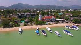 White lighthouse and parked speed boats near beach. HD aerial overflight view. Chalong, Phuket, Thailand. stock footage