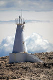 White lighthouse on a rock Stock Photos