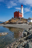 White Lighthouse on Rock Strewn Beach Stock Photos