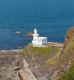 White Lighthouse on rocks royalty free stock image