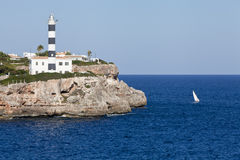 White lighthouse on rocks in the sea ocean water sky blue. Summer Stock Photo