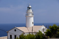 White lighthouse on rocks in the sea ocean water sky blue. Summer Royalty Free Stock Images