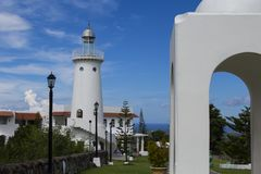 White lighthouse by rotunda in Greek architectural style. Tropical place resort with sea view. White gazebo and lighthouse summer park. Romantic wedding place Royalty Free Stock Photos
