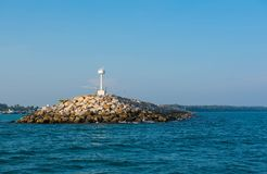 White  lighthouse in the sea in day time and blue sky background.  Stock Image