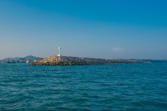 White  lighthouse in the sea in day time and blue sky background.  Stock Photography