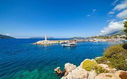 White lighthouse, sightseeing ship in blue sea in Kas, Turkey Stock Images