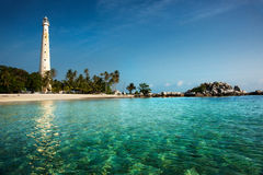 White lighthouse standing on an island in Belitung at daytime. White lighthouse standing on an island in Belitung at daytime surrounded by clear blue green Royalty Free Stock Photography