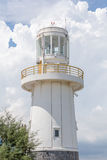 White lighthouse standing under the white fluffy cloudy sky. Royalty Free Stock Photography