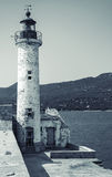 White lighthouse tower. Entrance to Propriano. Port, Corsica island, France. Monochrome toned, retro stylized photo Stock Photos