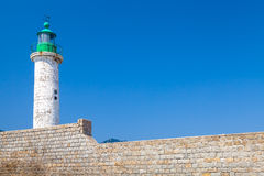 White lighthouse tower on stone pier Royalty Free Stock Images