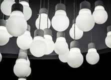White lighting ball hanging from the ceiling. On the black background Stock Photos