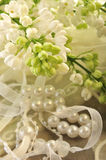 White lilacs and pearls. A wedding decoration with white ribbon, pearls and lilacs Stock Photos