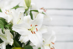 White lilies on light wooden background. Outdoor Royalty Free Stock Photography
