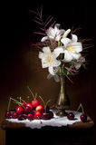 White Lily with Red Cherries Still life. White Lilies in a golden vase on a wooden table and a bunch of a sweet red cherries Stock Photography