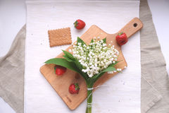 White lily of the valley bouquet and strawberries. The white lily of the valley bouquet on a wooden carving board with strawberries on beige linen Stock Photo