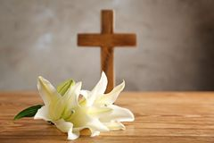 White lily and wooden cross. On table Royalty Free Stock Photos
