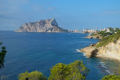 Costa Blanca bays and inlets with the town of Calpe and Calpe Rock, Ifach, in the distance, Spain. Royalty Free Stock Photography