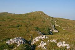White limestone rocks and the small trekking path. The mountain landscape with white limestone rocks and the small trekking path on the green hillside. This Stock Photography